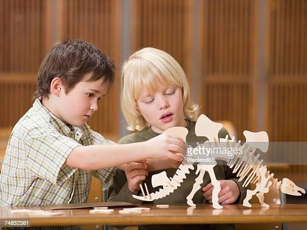 Boys (4-7) sitting with dinosaur skeleton, close-up