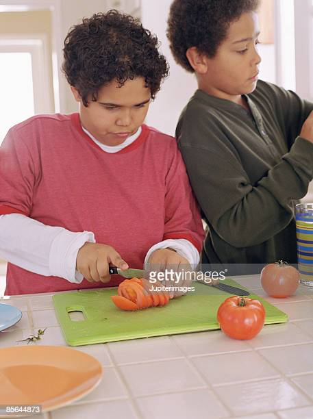 Boys slicing tomatoes