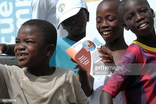 Boys smile as one reads an Ebola prevention flyer in a suburb of Dakar on September 11 2014 A Guinean student who was Senegal's only confirmed case...