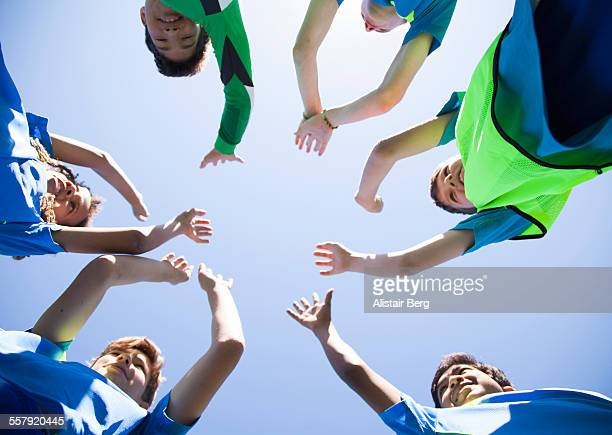 Boys soccer team doing high five before a game