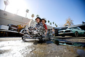 Boys splashing through mudpuddle