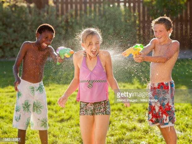 Boys squirting girl with water guns