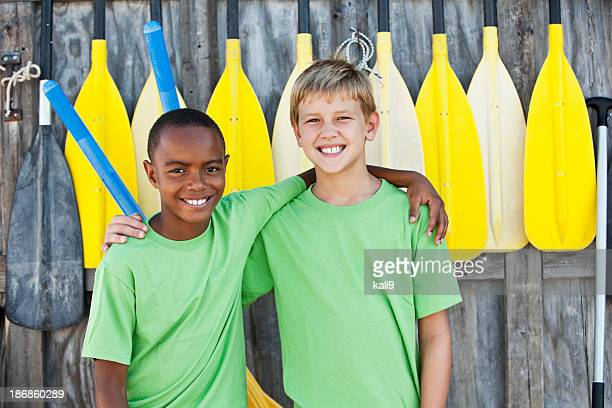 Boys standing in front of paddles