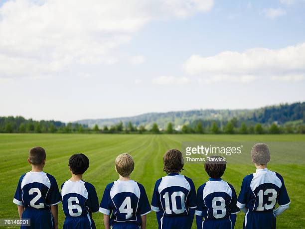 Boys (10-11, 12-13) standing in row in field, rear view, elevated view