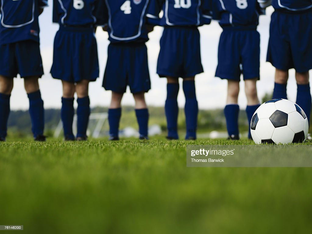 Boys (10-13) standing in row on football pitch, low section : Stock Photo