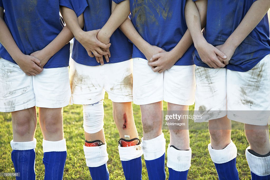 Boys (9-11) standing on soccer team, mid section : Stock Photo
