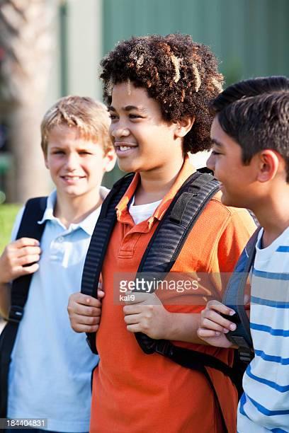 Ragazzi in piedi fuori scuola con cartella,