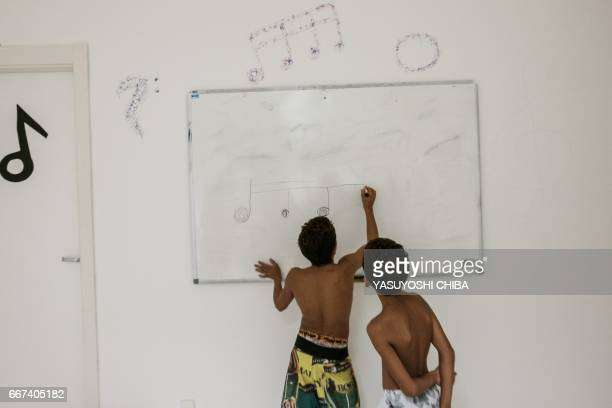 Boys take a free music class inside a station of the cable car system which is no longer running over the Alemao favela in Rio de Janeiro Brazil on...
