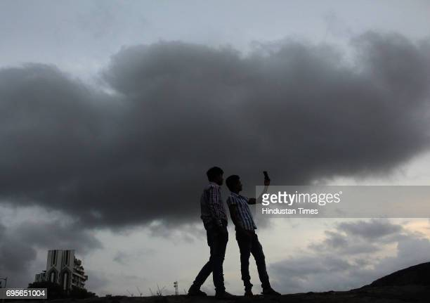Boys take selfie under a cloudy sky at Dadar Chowpatty on June 12 2017 in Mumbai India The muchawaited Southwest Monsoon has finally made an...