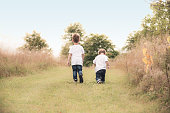 Two young boys take a leisurely stroll down a country meadow.  This image symbolizes what youth is all about, being fancy free and having a bright sunny future in front of you.  Lots of space for copy