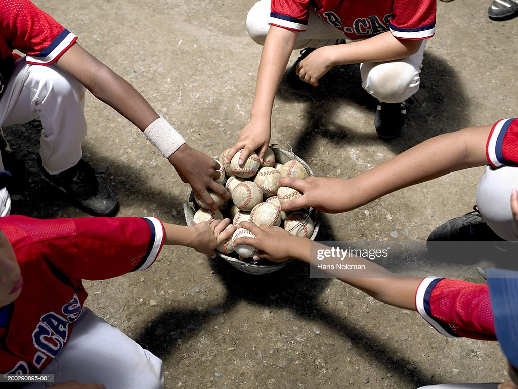 Boys (8-10) taking baseballs out of bucket, elevated view : Stock Photo