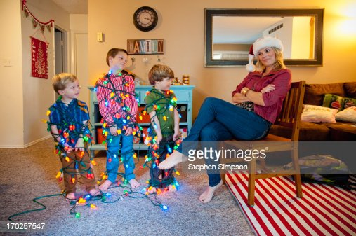 Boys Tied Up In Strings Of Christmas Lights Stock Photo