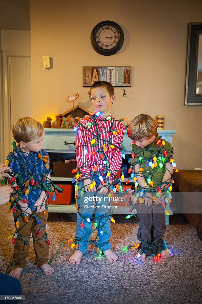 boys tied up in strings of Christmas lights : Stock Photo