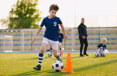 Boys training football dribbling in a field. Kids Running the Ball. Players develop soccer dribbling skills. Children training with balls and cones. Soccer slalom drills