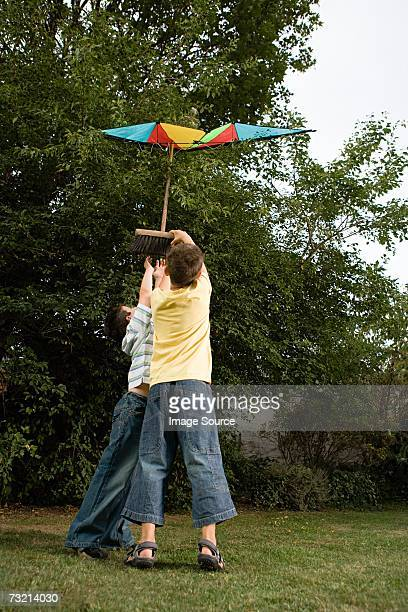 Boys trying to get kite from tree