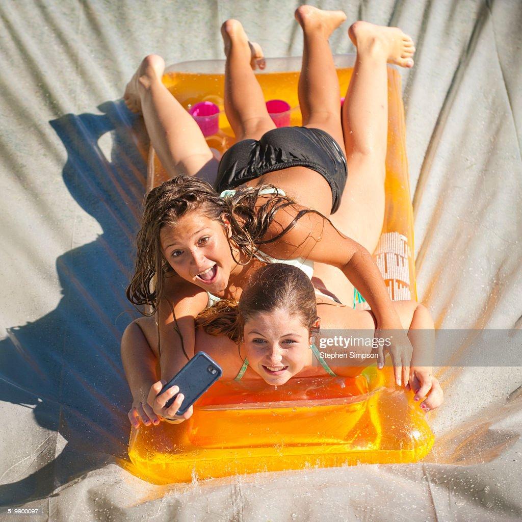 boys tumbling down backyard downhill slip n slide stock photo