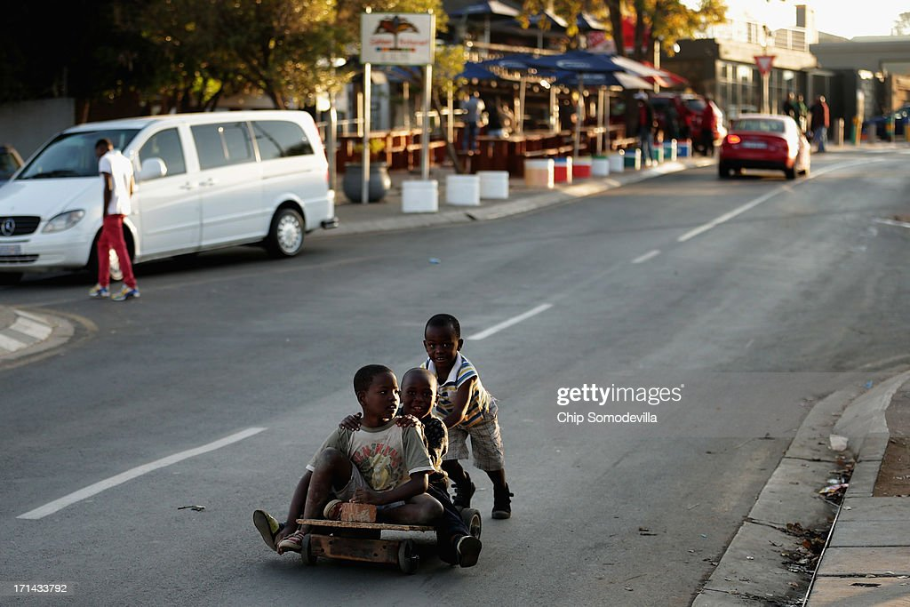 Boys use a homemade skateboard to roll down Vilakazi Street from former President Nelson Mandela's Soweto home, which now serves as a museum, June 24, 2013 in Johannesburg, South Africa. South African President Jacob Zuma confirmed that Mandela's condition has become critical since he was admitted to the hospital over two weeks ago for a recurring lung infection.