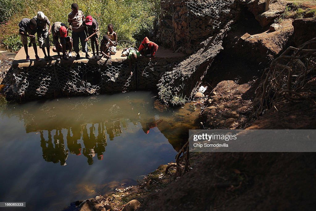 Boys use string and hooks while trying to catch frogs and crabs in a creek running through Thokoza Park April 8, 2013 in Johannesburg, South Africa. Thokoza Park is situated right next to Regina Mundi Catholic Church, a site of resistance during apartheid and place of shelter during the 1976 Soweto Uprising. Former South African President Nelson Mandela returned to his Johannesburg home Saturday after spending nine days in the hospital with pneumonia.