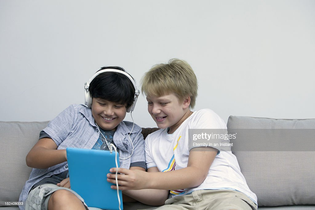 Boys using a digital tablet device with headphones : Stock Photo