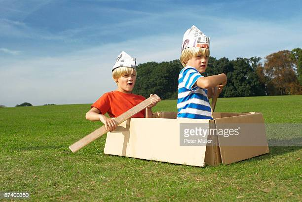 boys using box as imaginary boat