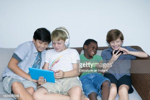 Boys using smartphones and digital tablets : Bildbanksbilder