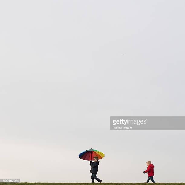 Boys walking, holding an umbrella