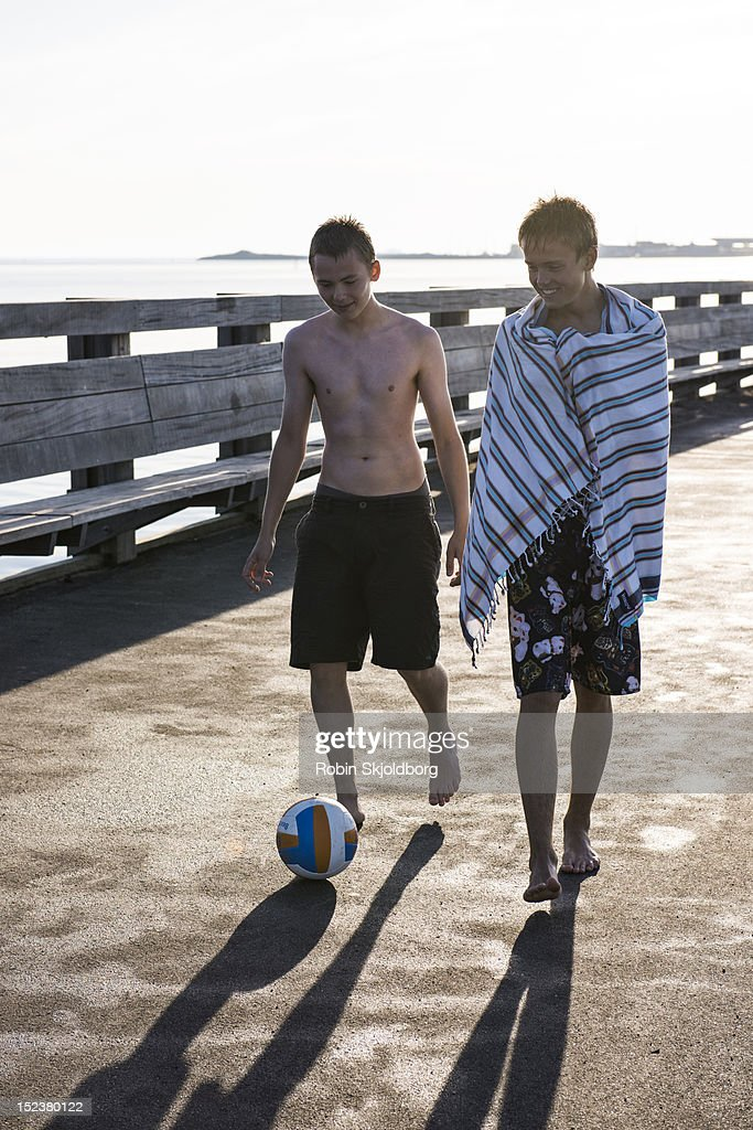 Boys walking in swimming trunks with ball : Stock Photo