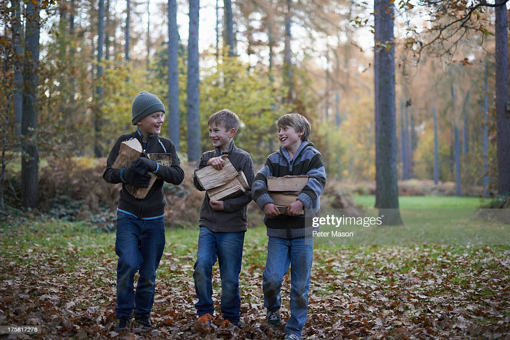 Boys walking through forest carrying wood : Stock Photo