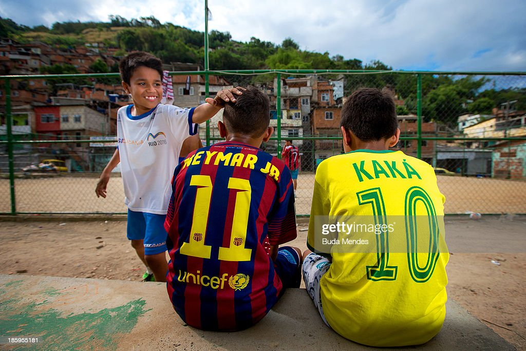 Boys wear jerseys bearing the names of Brazilian team players of Neymar Jr and Kaka while watching a match at the Vila Nova Project in the Morro dos Macacos area on October 26, 2013 in Rio de Janeiro, Brazil. The Project Vila Nova was idealized by Alex Sandro and has so far run for 2 years, catering to children and young residents of the Morro dos Macacos area.