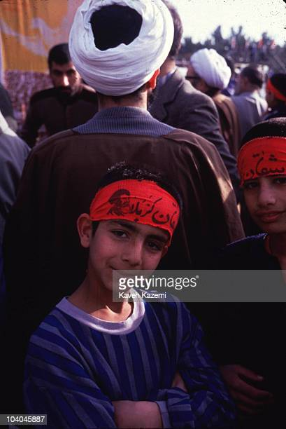 Boys wearing headbands bearing religious inscriptions stand in front of a Muslim cleric at a rally during the IranIraq War at Shiroudi stadium in...