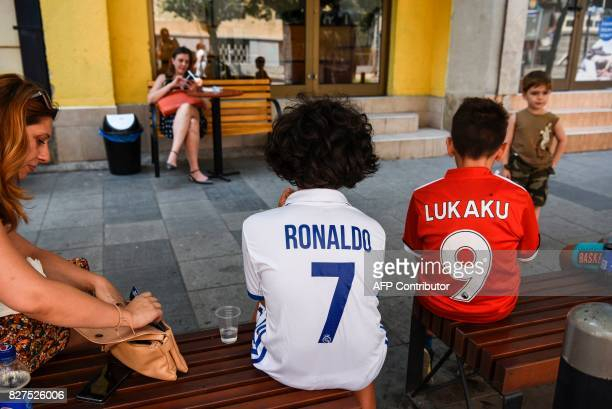 Boys wearing Real Madrid's and Manchester United jerseys sit on a bench in Skopje on August 8 2017 ahead of the UEFA Super Cup football match between...