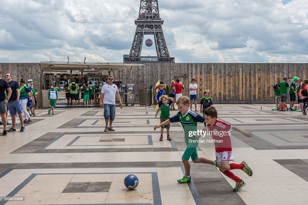 Boys wearing team uniforms of Wales and Northern Ireland play football near the Eiffel Tower as fans prepare to watch the football match between Wales and Northern Ireland during UEFA Euro 2016 tournament on June 25, 2016 in Paris, France. Wales edged Northern Ireland in the Round of 16 at Parc des Princes in Paris.