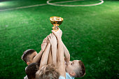 Stretched arms of little footballers holding gold award on background of green pitch