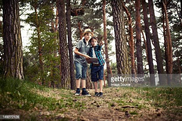 Boys with digital tablet in forest