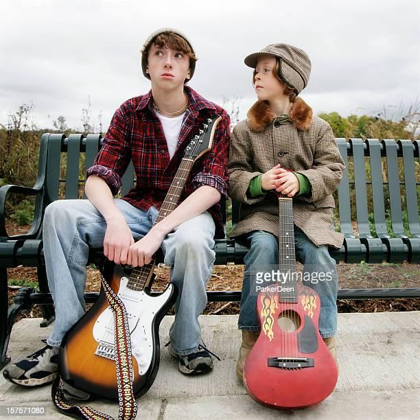 Jungen mit Gitarren, auf einer Bank sitzend
