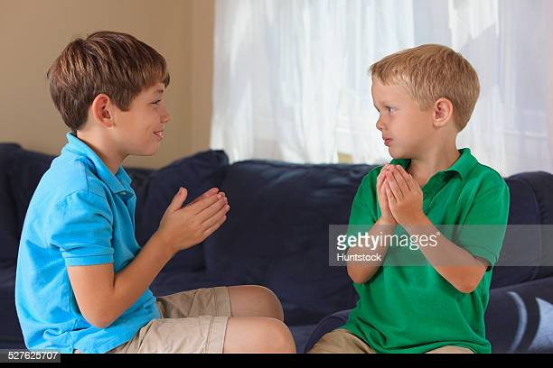 Boys with hearing impairments signing boat in American sign language on their couch