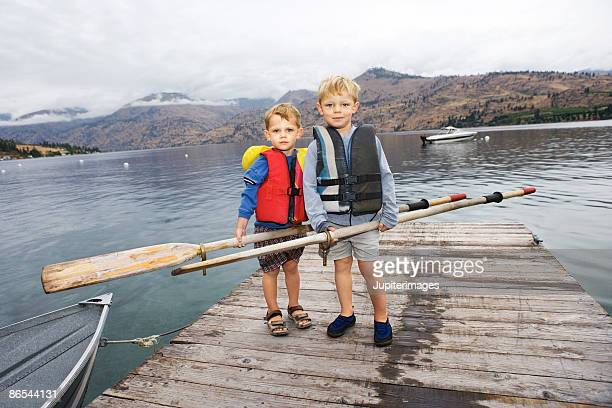 Boys with oars on dock