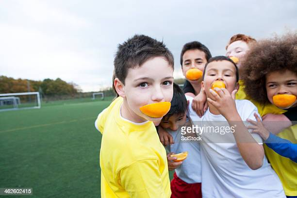 Boys With Oranges In Their Mouths On A Soccer Field