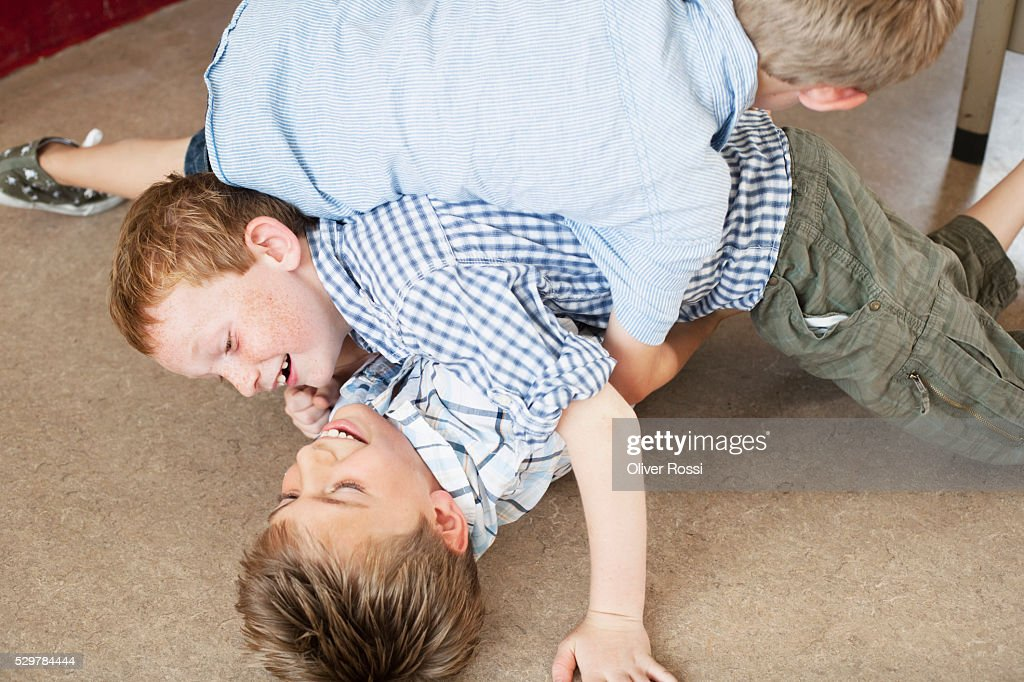 Boys wrestling on floor in classroom : Stock Photo