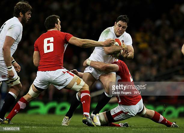 Brad Barritt of England is hauled down by Sam Warburton and Ian Evans of Wales during the RBS Six Nations match between Wales and England at...