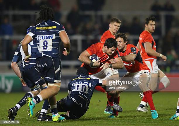 Brad Barritt of Saracens is tackled by Alan MacGinty of Sale Sharks during the European Rugby Champions Cup match between Sale Sharks and Saracens at...