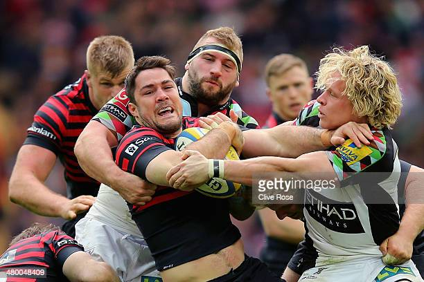 Brad Barritt of Saracens is trackled by Joe Marler and Matt Hopper of Harlequins during the Aviva Premiership match between Saracens and Harlequins...