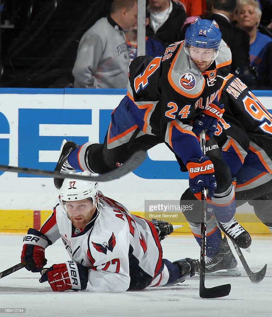 Brad Boyes #24 of the New York Islanders jumps out of the way of a sliding Karl Alzner #27 of the Washington Capitals during the first period at the Nassau Veterans Memorial Coliseum on March 9, 2013 in Uniondale, New York.