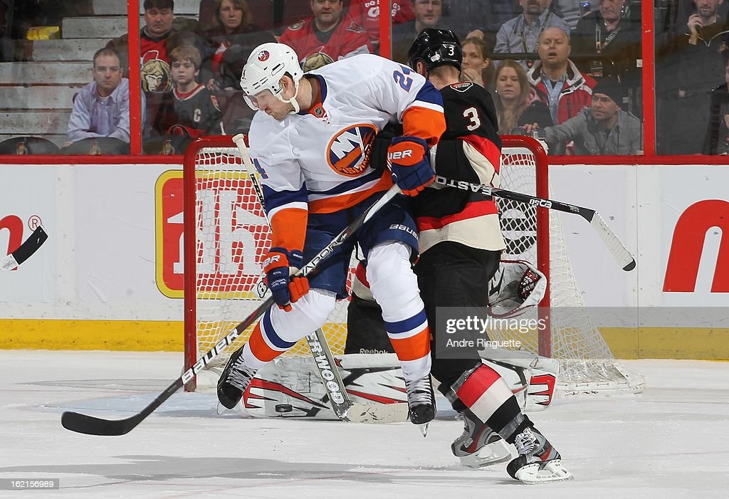 <a gi-track='captionPersonalityLinkClicked' href=/galleries/search?phrase=Brad+Boyes&family=editorial&specificpeople=275014 ng-click='$event.stopPropagation()'>Brad Boyes</a> #24 of the New York Islanders jumps to avoid being hit by the puck as he screens the goalie while <a gi-track='captionPersonalityLinkClicked' href=/galleries/search?phrase=Marc+Methot&family=editorial&specificpeople=2216900 ng-click='$event.stopPropagation()'>Marc Methot</a> #3 of the Ottawa Senators defends against on February 19, 2013 at Scotiabank Place in Ottawa, Ontario, Canada.