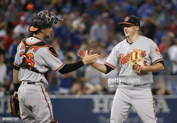 Brad Brach of the Baltimore Orioles celebrates their victory with Caleb Joseph during MLB game action against the Toronto Blue Jays at Rogers Centre...