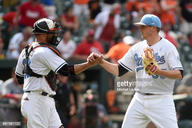 Brad Brach of the Baltimore Orioles celebrators a win with Welington Castillo of the Baltimore Orioles after a baseball game against the St Louis...