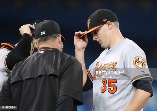 Brad Brach of the Baltimore Orioles is visited on the mound by bench coach John Russell in the eighth inning during MLB game action against the...