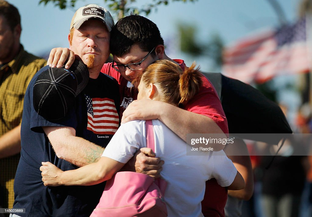 Brad Cooley, Austin Stapleton and Misty Pietrzak (L-R) hug in Cunningham Park during a moment of silence at 5:41 p.m. which was when the monstrous tornado first hit the city a year ago to the day on May 22, 2012 in Joplin, Missouri. The EF-5 tornado devastated the area leaving behind a path of destruction along with 161 deaths and hundreds of injuries, but one year later there are signs that the town is beginning to recover.