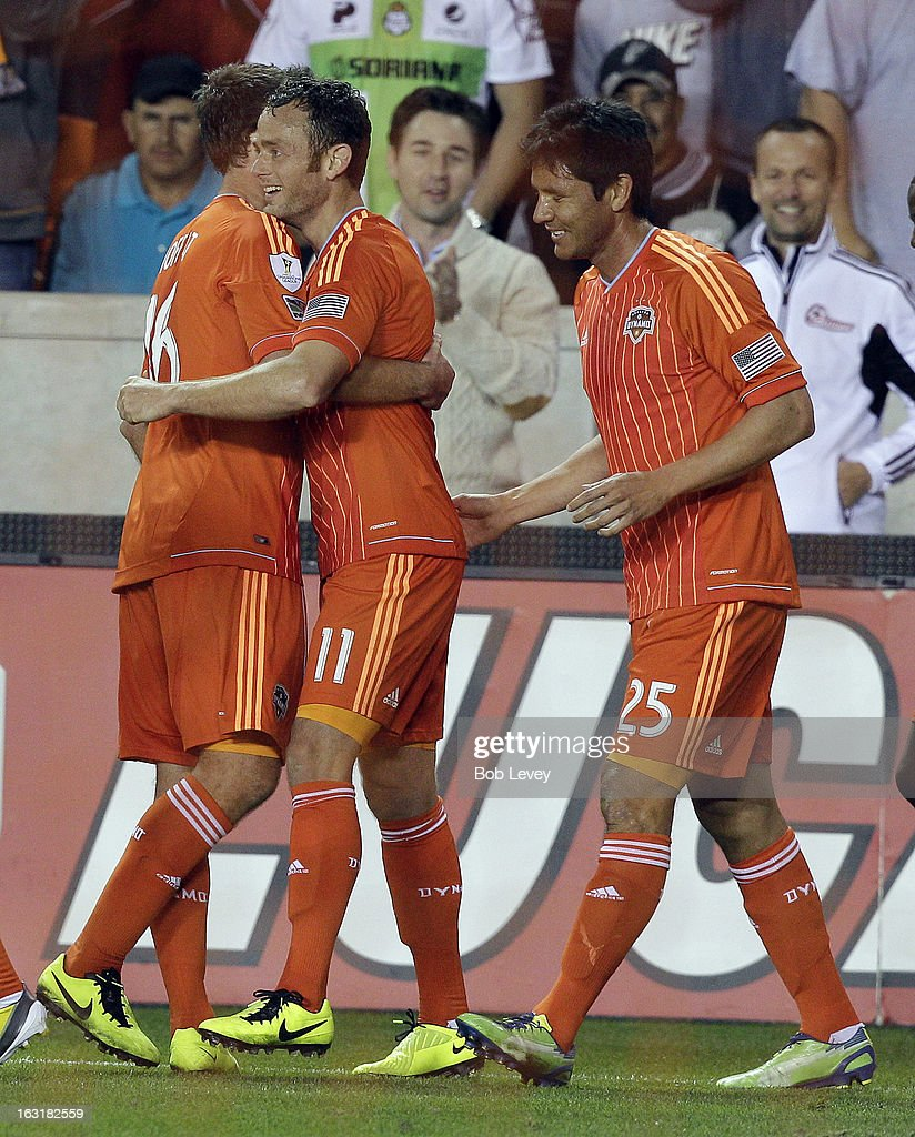Brad Davis #11 of Houston Dynamo celebrates with Adam Moffat #16 and <a gi-track='captionPersonalityLinkClicked' href=/galleries/search?phrase=Brian+Ching&family=editorial&specificpeople=453218 ng-click='$event.stopPropagation()'>Brian Ching</a> #25 after scoring in the 89th minute against Santos Laguna during the second half at BBVA Compass Stadium on March 5, 2013 in Houston, Texas.