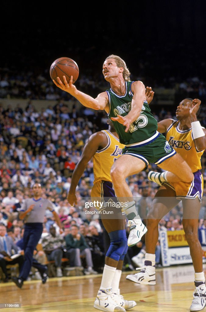 Brad Davis of the Dallas Mavericks leaps between two members of the Los Angeles Lakers to shoot the ball during the NBA game at the Great Western...